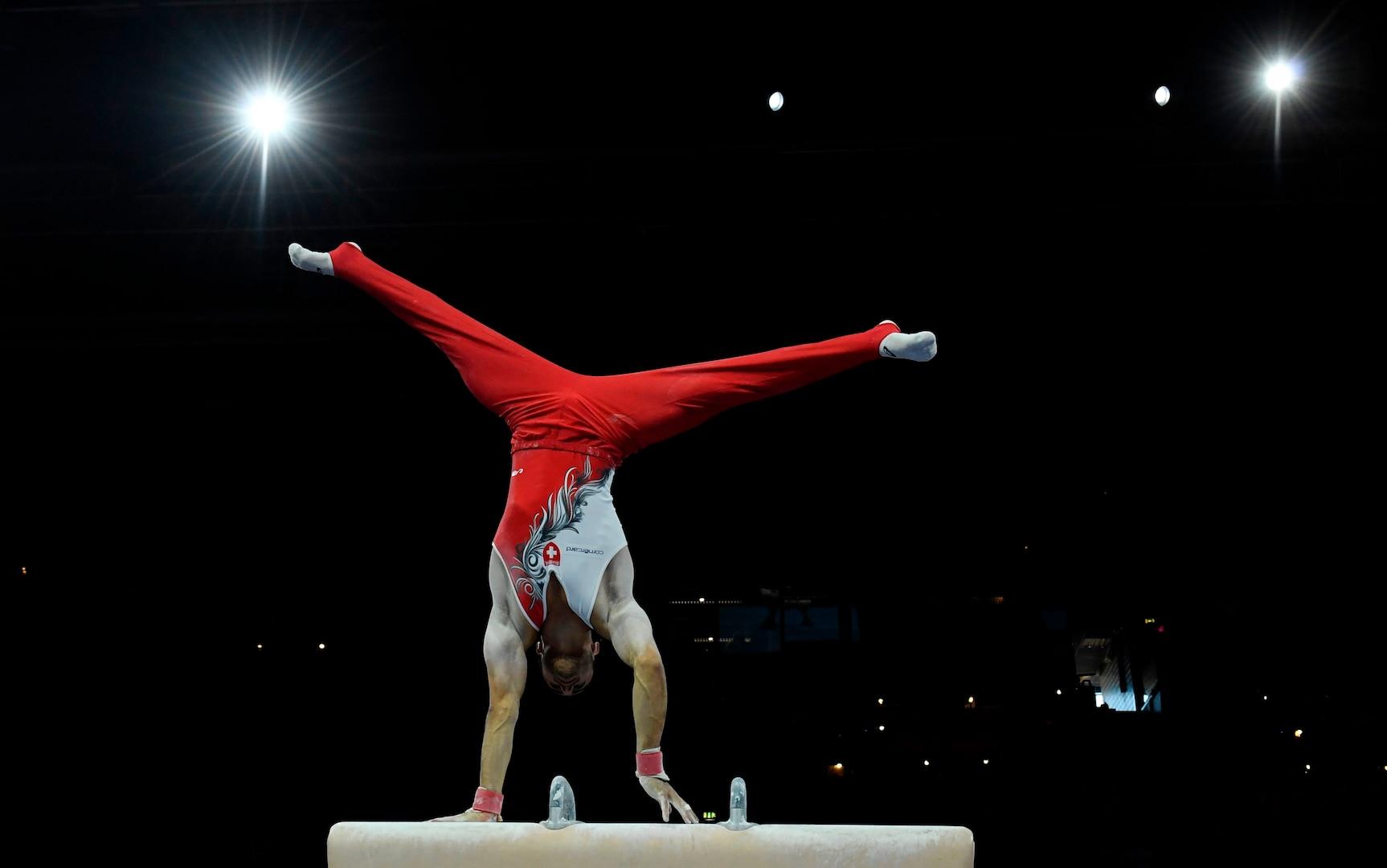 A gymnast performs on pommel horse.