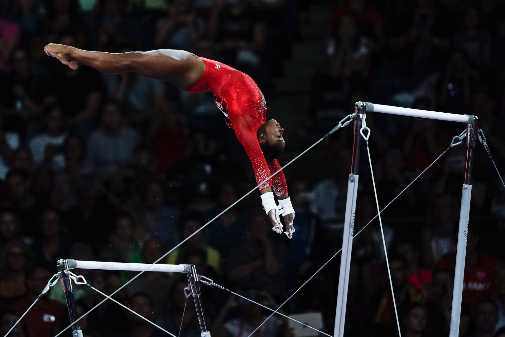 A gymnast travels between the low and high uneven bars.
