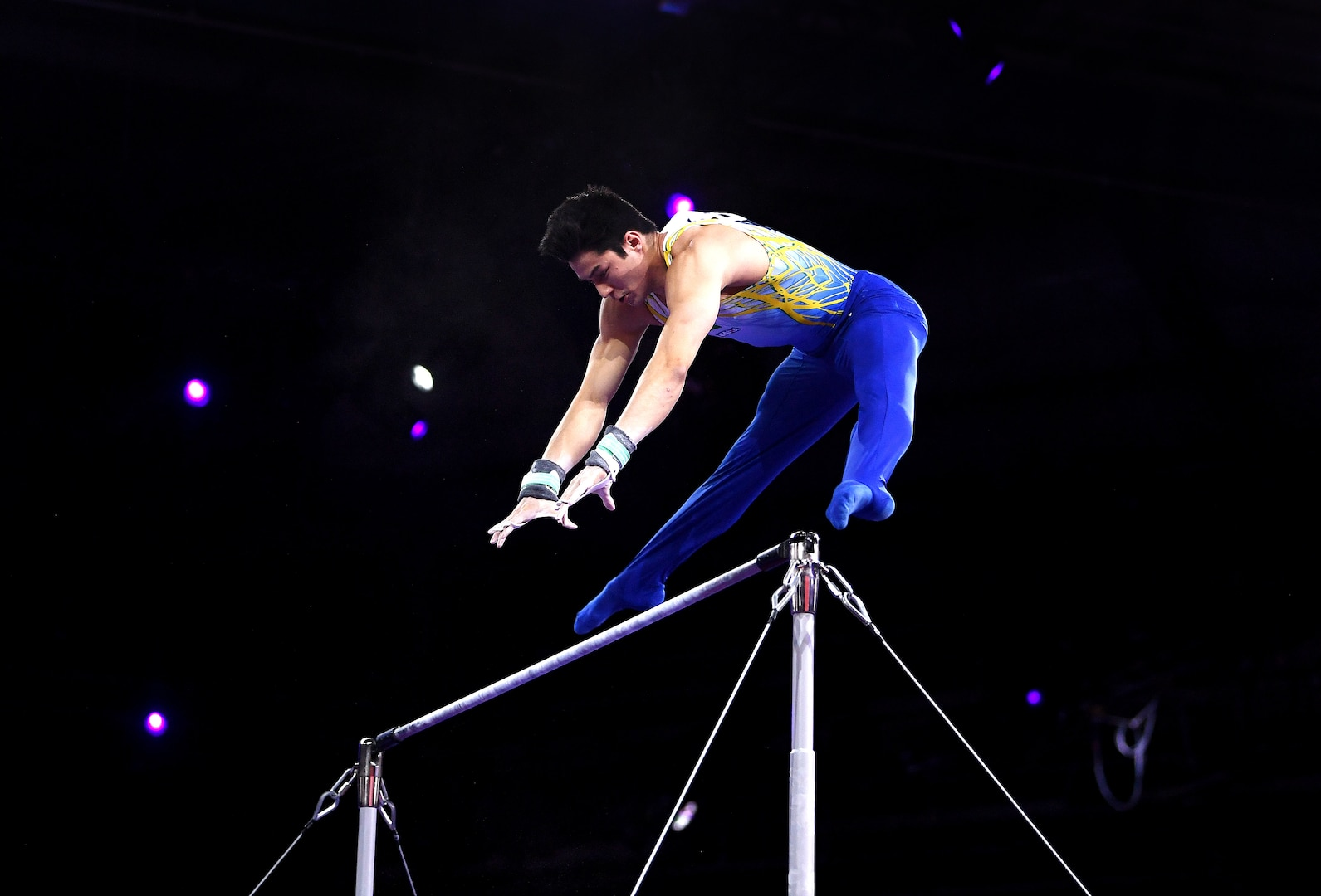 A gymnast begins to catch the high bar from a straddle position.