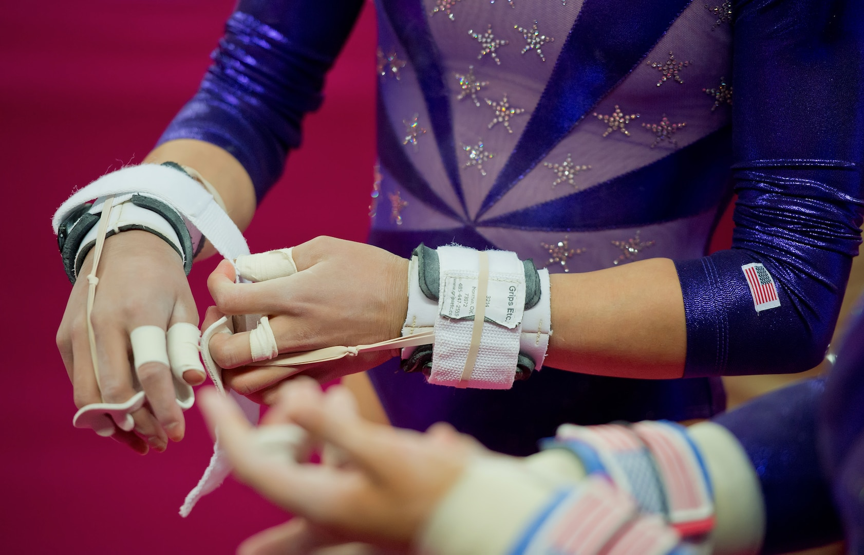 A gymnast adjusts her hand grips in preparation for an uneven bars routine.
