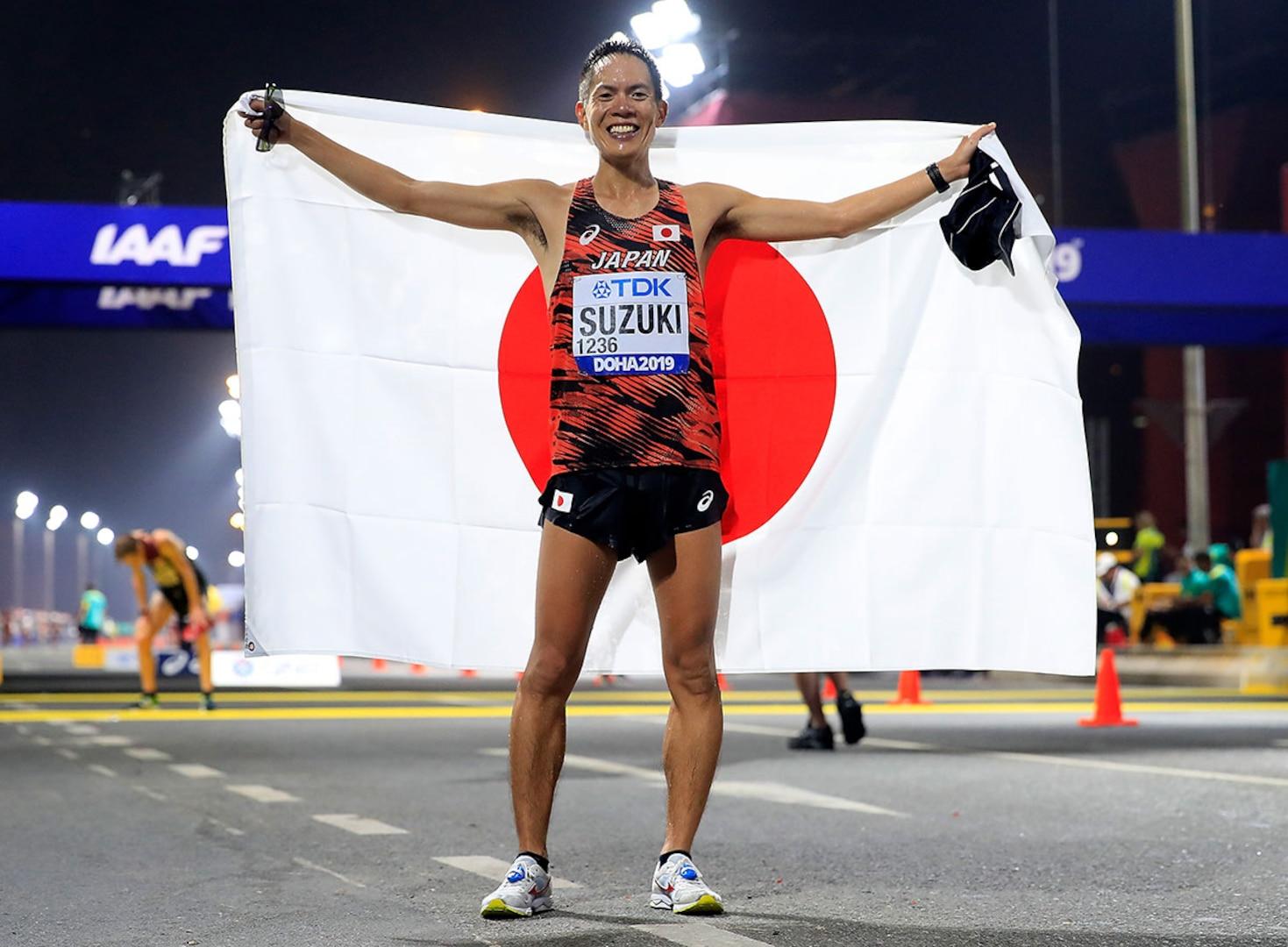 Yusuke Suzuki celebrates with the Japanese flag after winning a world title