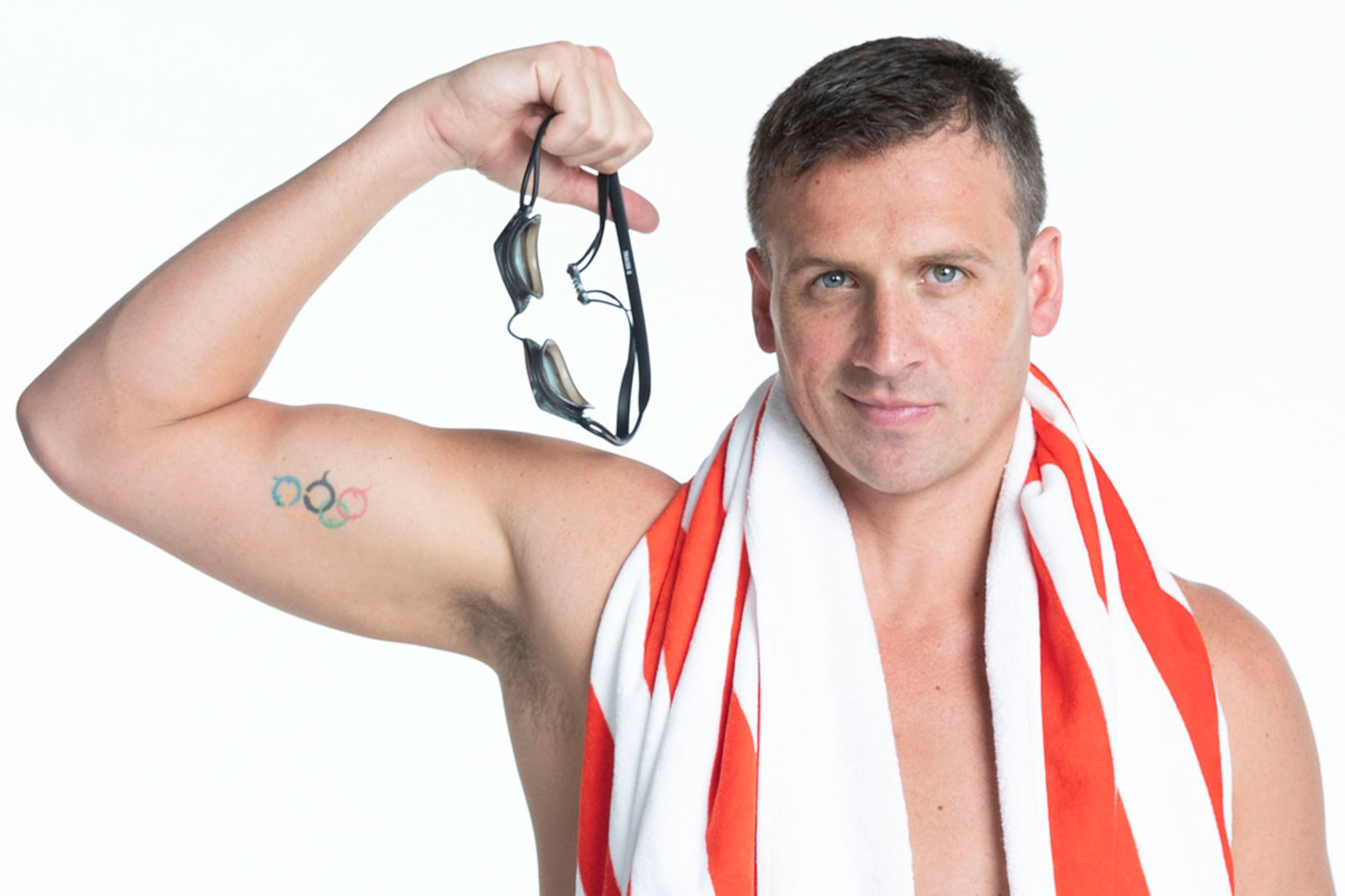 Ryan Lochte flexes and shows the Olympic ring tattoo on his bicep