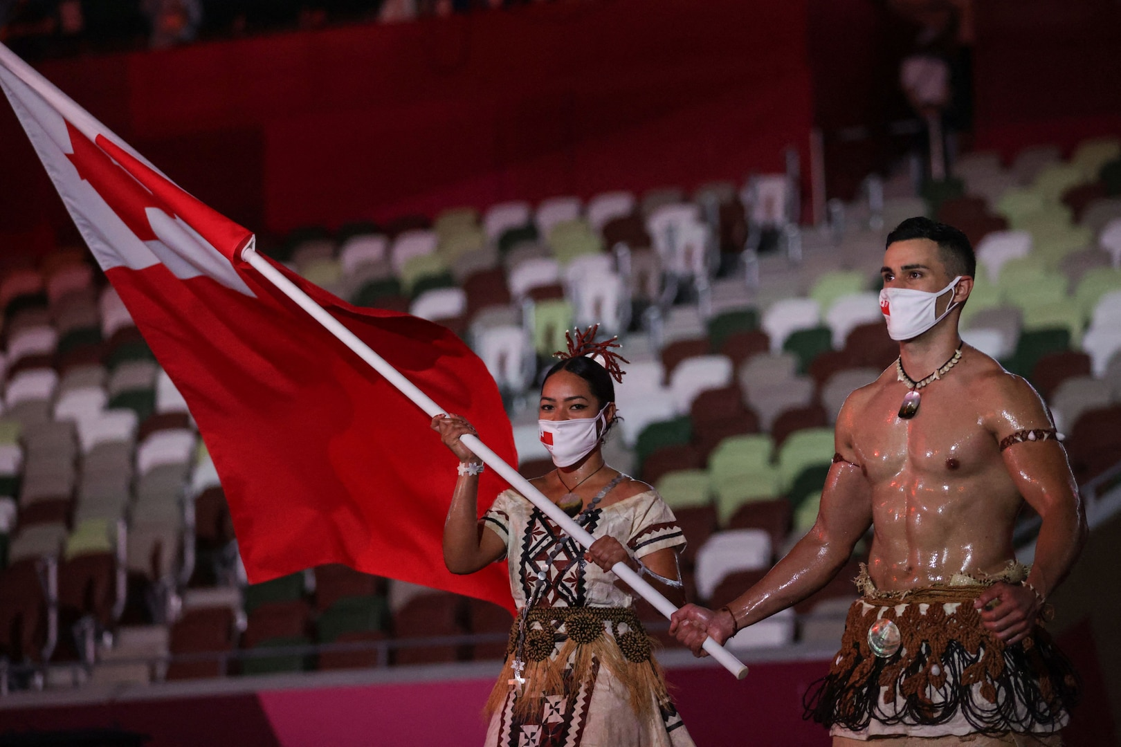 Tonga's flag bearers Malia Paseka (L) and Pita Taufatofua lead the delegation during the Tokyo 2020 Olympic Games opening ceremony's parade of athletes, at the Olympic Stadium in Tokyo on July 23, 2021.