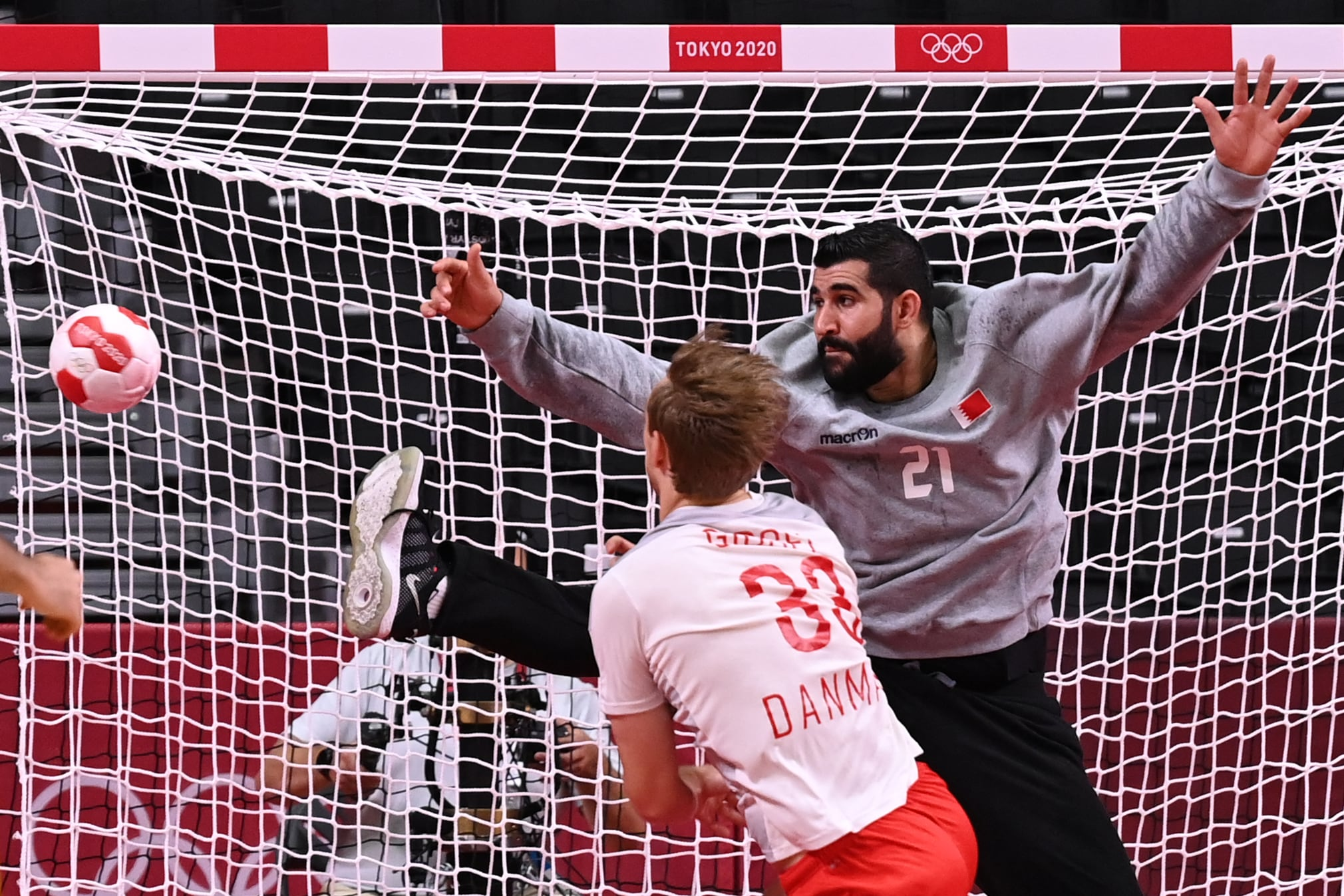Bahrain's goalkeeper Mohamed A.Husain (R) fails to stop a shot during the men's preliminary...