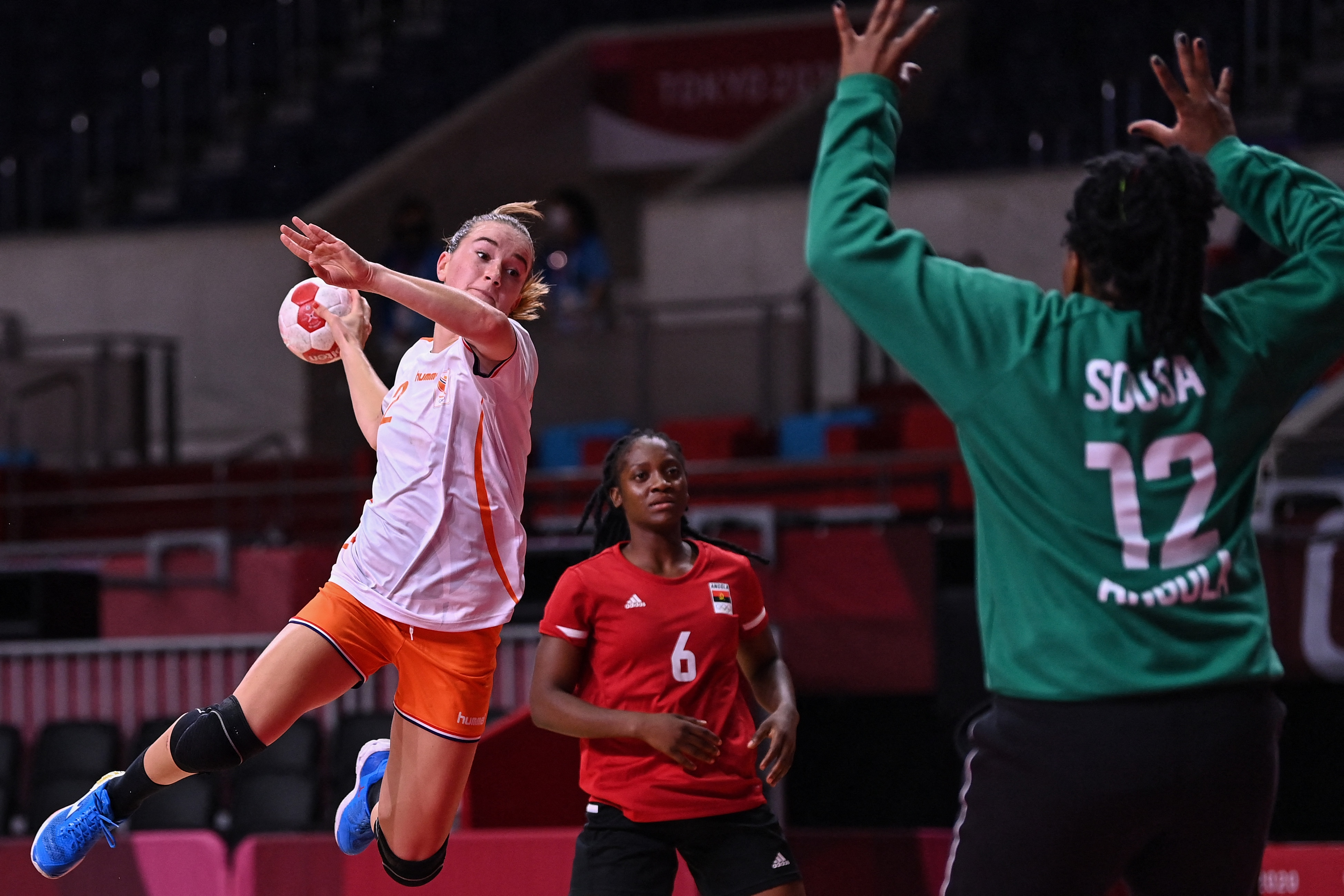 Netherlands' left wing Bo van Wetering (L) jumps to shoot during the women's preliminary round...