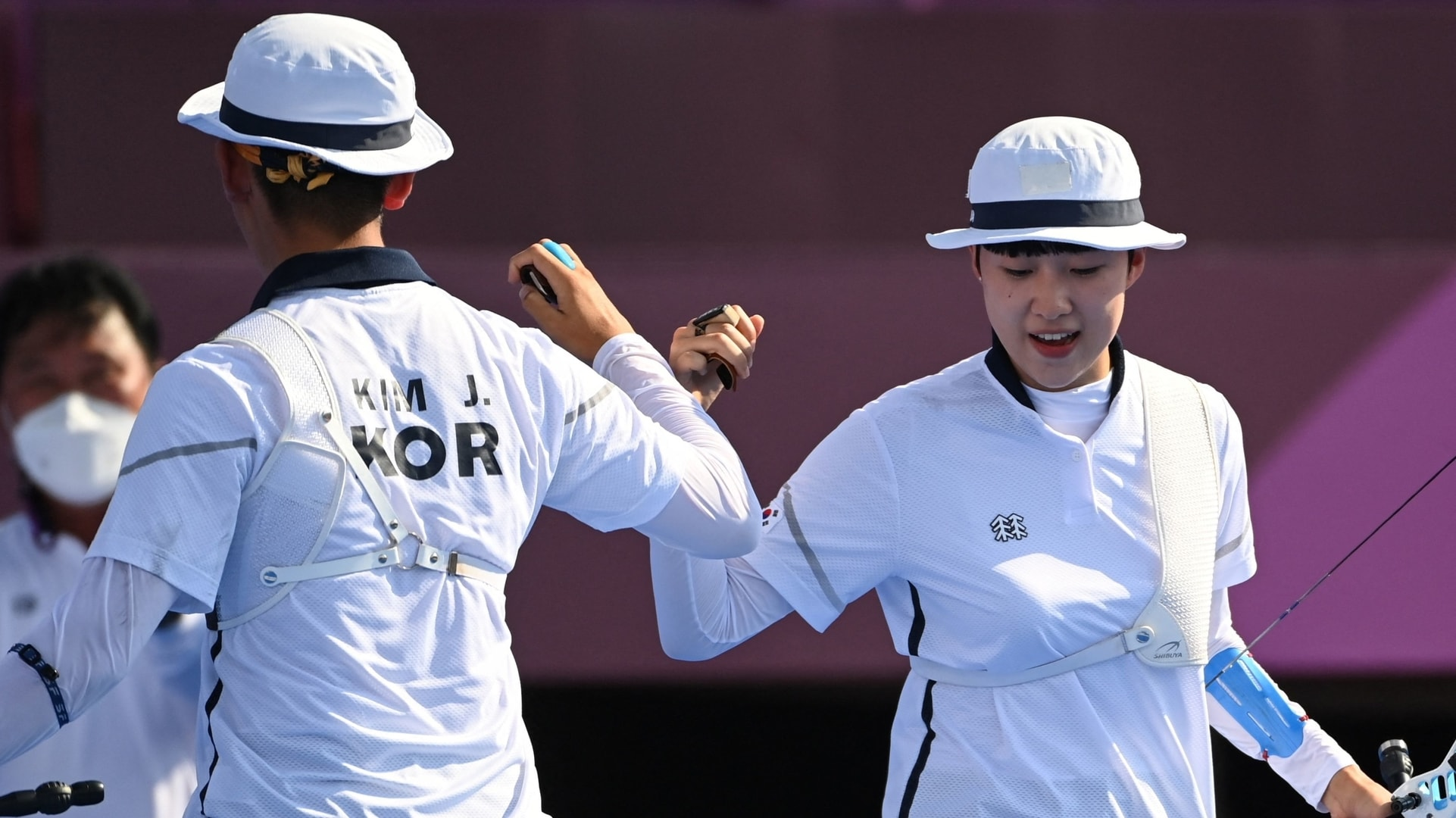 South Korea's Je-doek Kim (L) and San An react while competing in the mixed team...