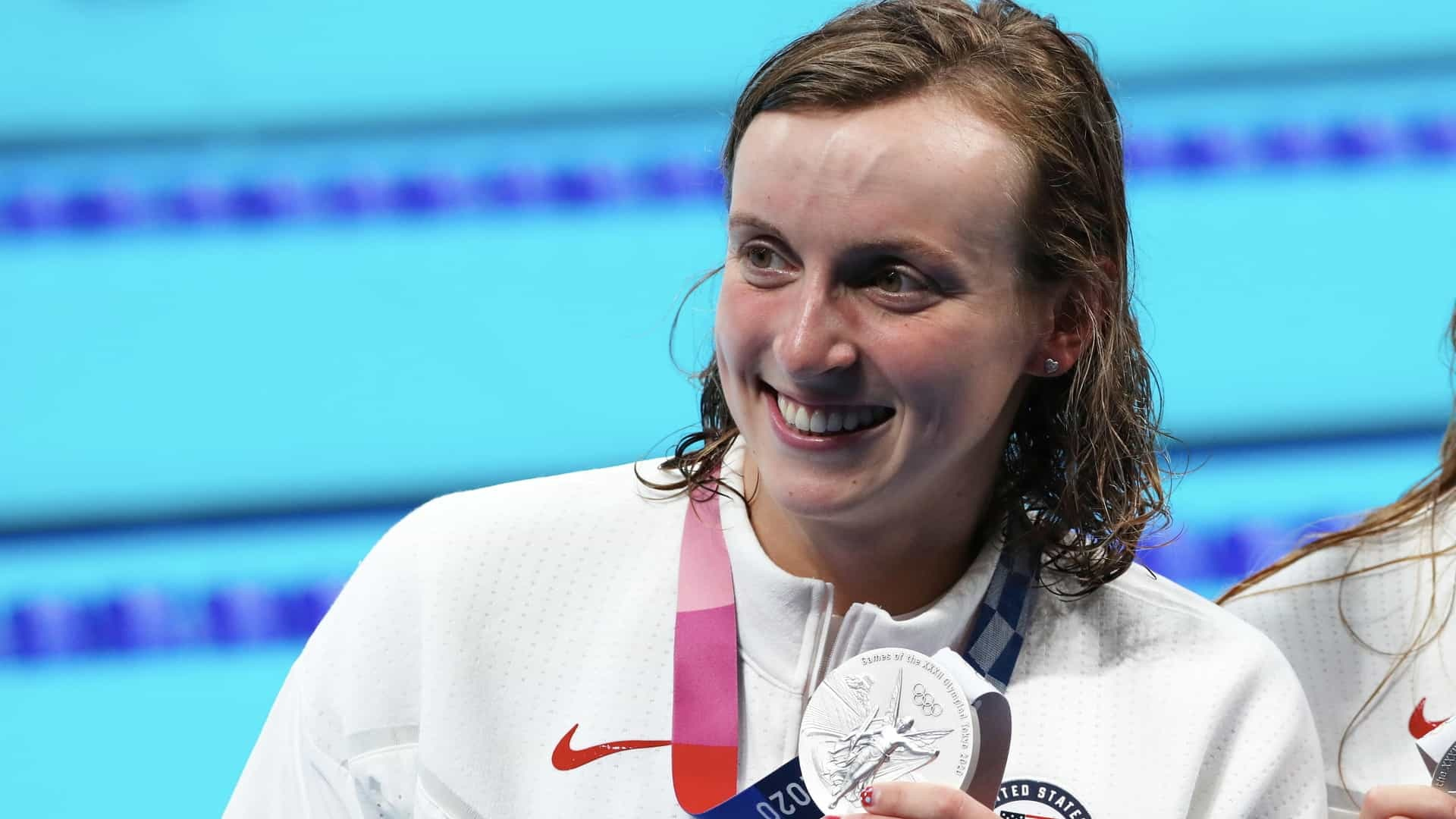 Katie Ledecky proudly shows off the silver medal she earned in the 4x200m freestyle relay at the 2020 Tokyo Olympic Games.