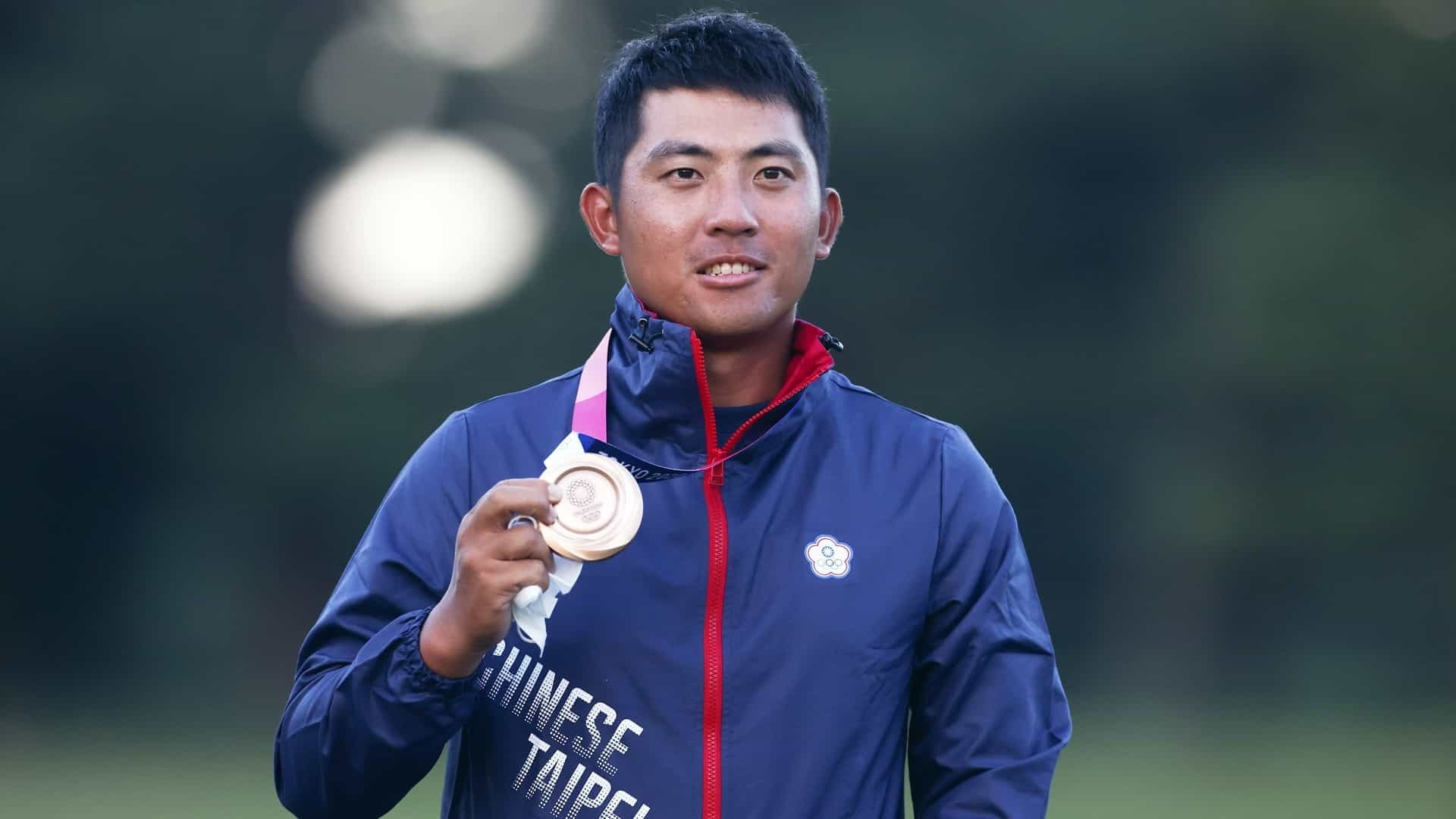 C.T. Pan of Thailand celebrates with his bronze medal in the men's golf tournament at the 2020 Tokyo Olympic Games.