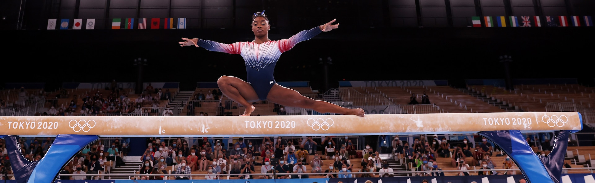 Simone Biles on balance beam with one leg stretched out