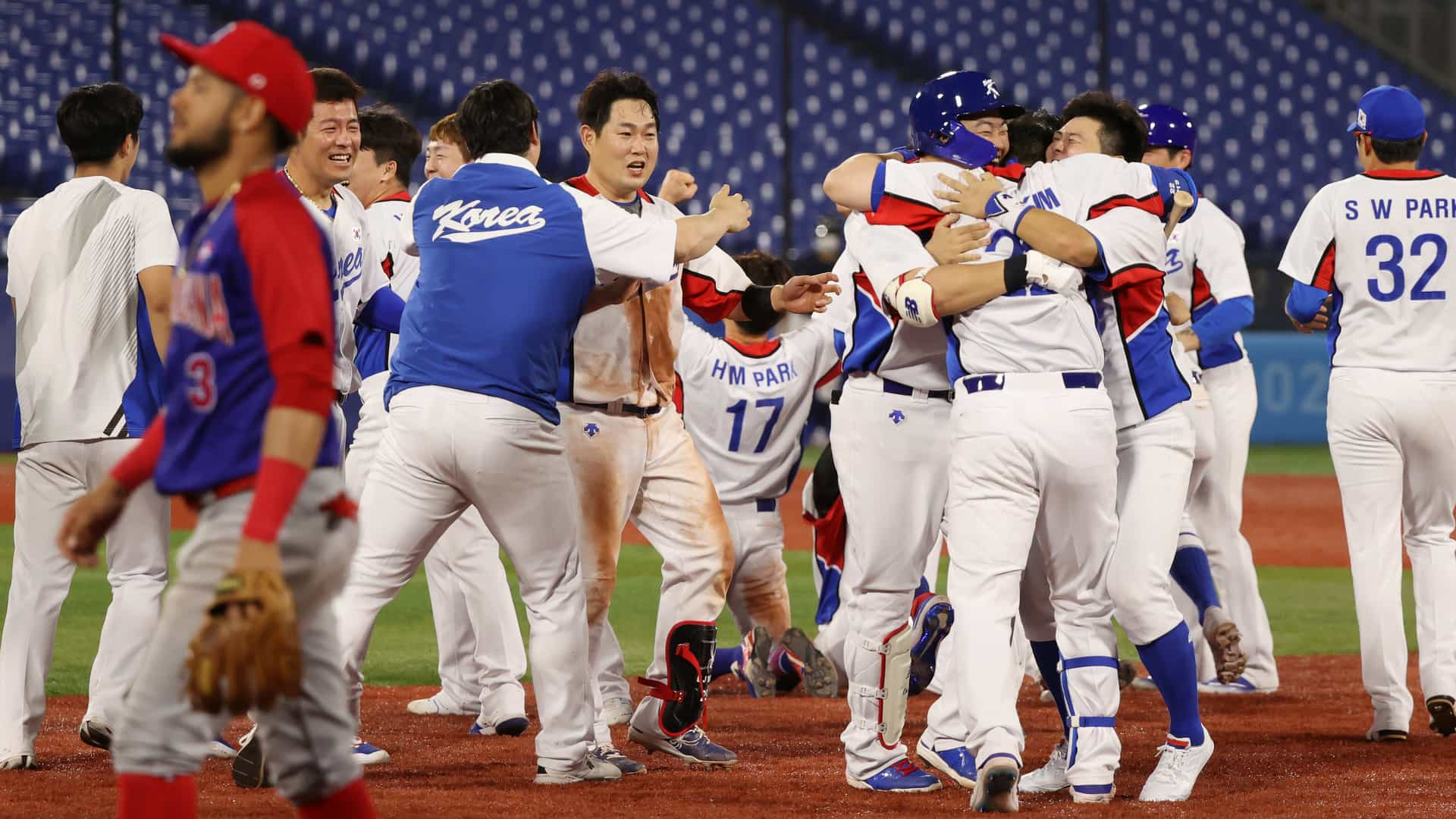 South Korean players rush to celebrate their walk-off win over the Dominican Republic in Olympic baseball playoff action Sunday.